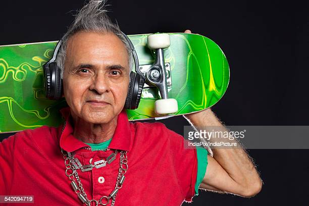 Close-up portrait of old man with skateboard