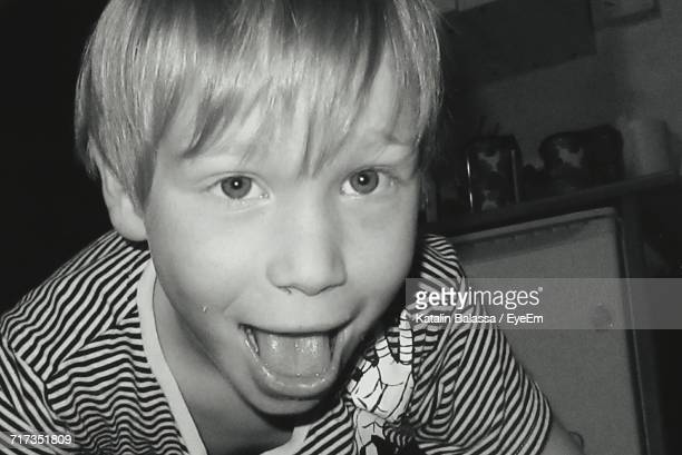 Close-Up Portrait Of Playful Boy Showing Tongue At Home