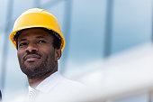 Close-up portrait of professional architect in hard hat looking away