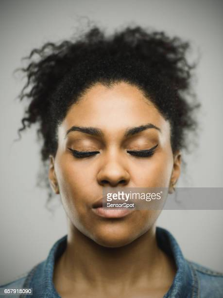 Close-up portrait of real young black woman with eyes closed