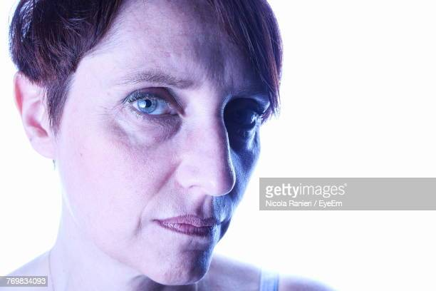 Close-Up Portrait Of Serious Mature Woman Against White Background