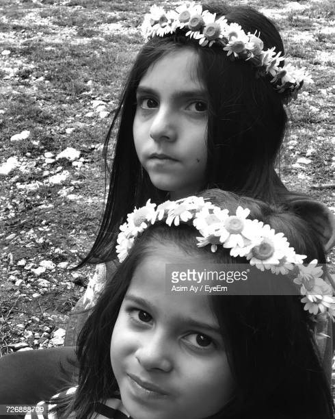 Close-Up Portrait Of Sisters Wearing Flowers While Sitting On Field