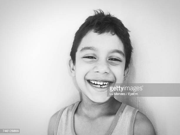 Close-Up Portrait Of Smiling Boy Against Wall