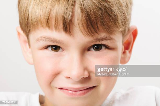 Close-Up Portrait Of Smiling Boy Against White Background