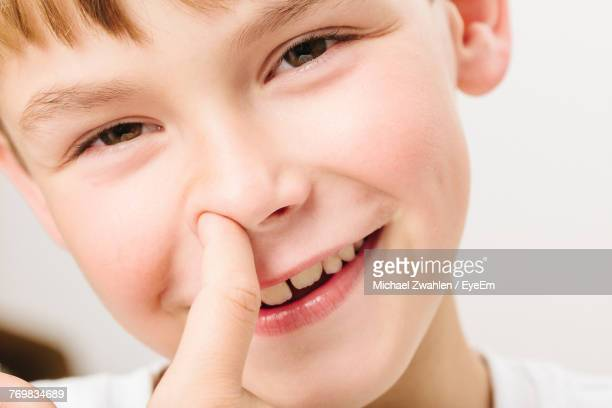 Close-Up Portrait Of Smiling Boy With Finger In Nose Against White Background