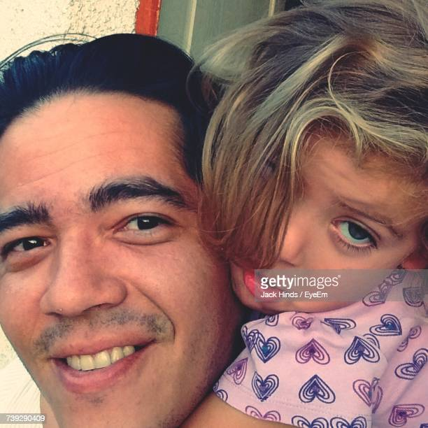 Close-Up Portrait Of Smiling Father With Cute Daughter