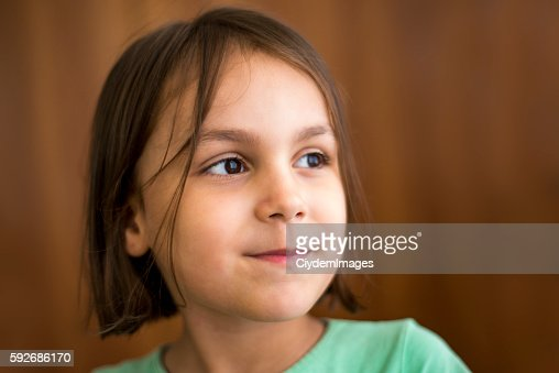 Close-up portrait of smiling little girl looking away