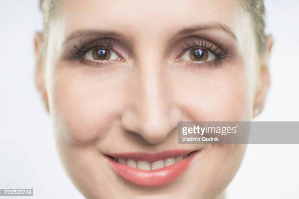 Close-up portrait of smiling mid adult woman against white background
