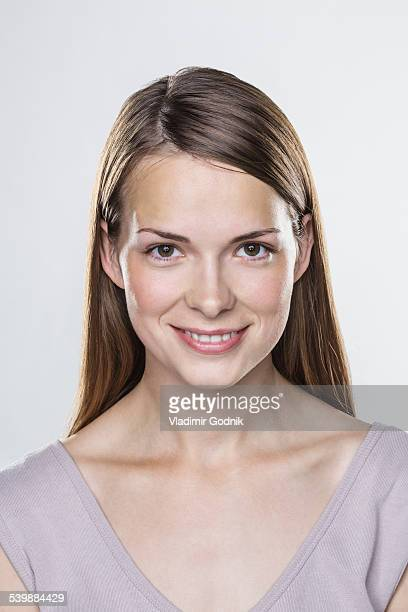 Close-up portrait of smiling young woman against white background