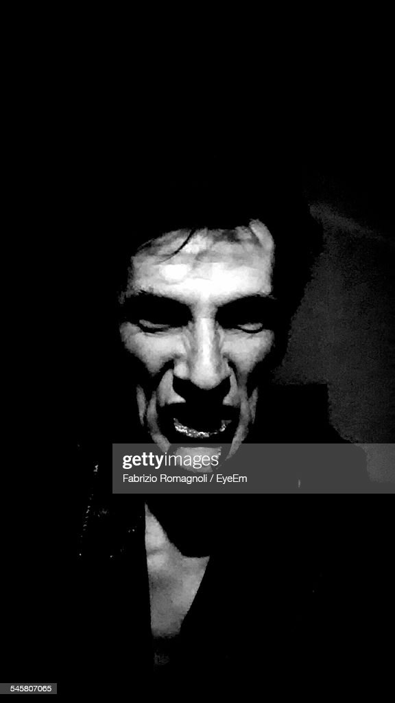 Close-Up Portrait Of Vampire In Darkroom