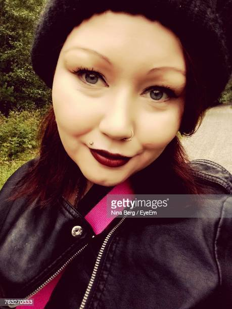 Close-Up Portrait Of Woman Wearing Black Leather Jacket On Footpath