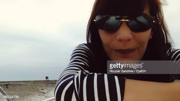 Close-Up Portrait Of Woman Wearing Sunglasses At Beach