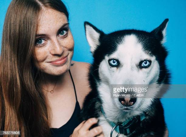 Close-Up Portrait Of Woman With Siberian Husky Against Blue Background