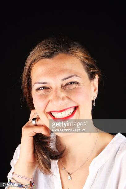 Close-Up Portrait Of Woman With Toothy Smile Against Black Background