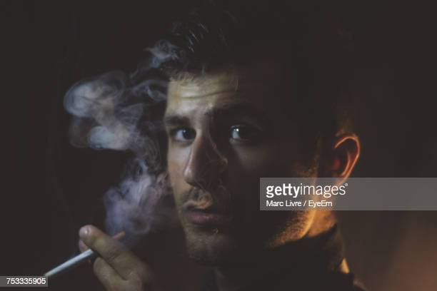 Close-Up Portrait Of Young Man Smoking Cigarette In Darkroom