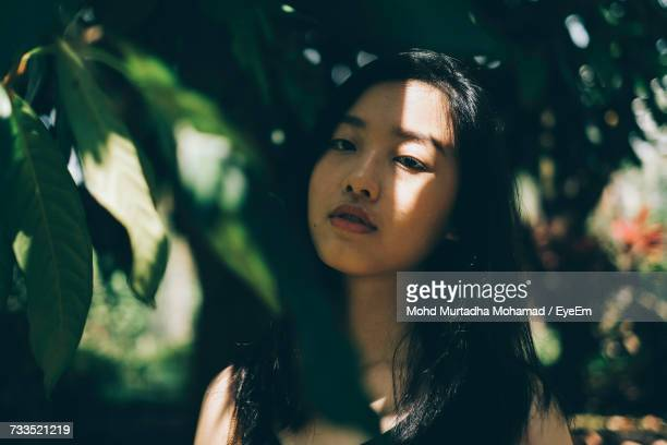 Close-Up Portrait Of Young Woman Against Tree