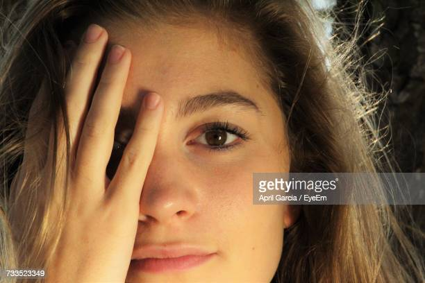 Close-Up Portrait Of Young Woman Covering Face