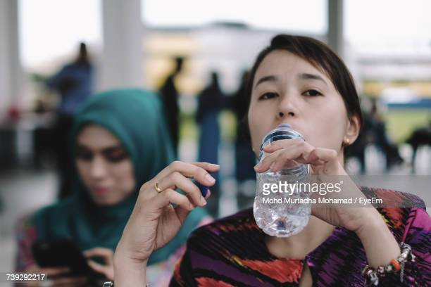 Close-Up Portrait Of Young Woman Drinking Water From Bottle