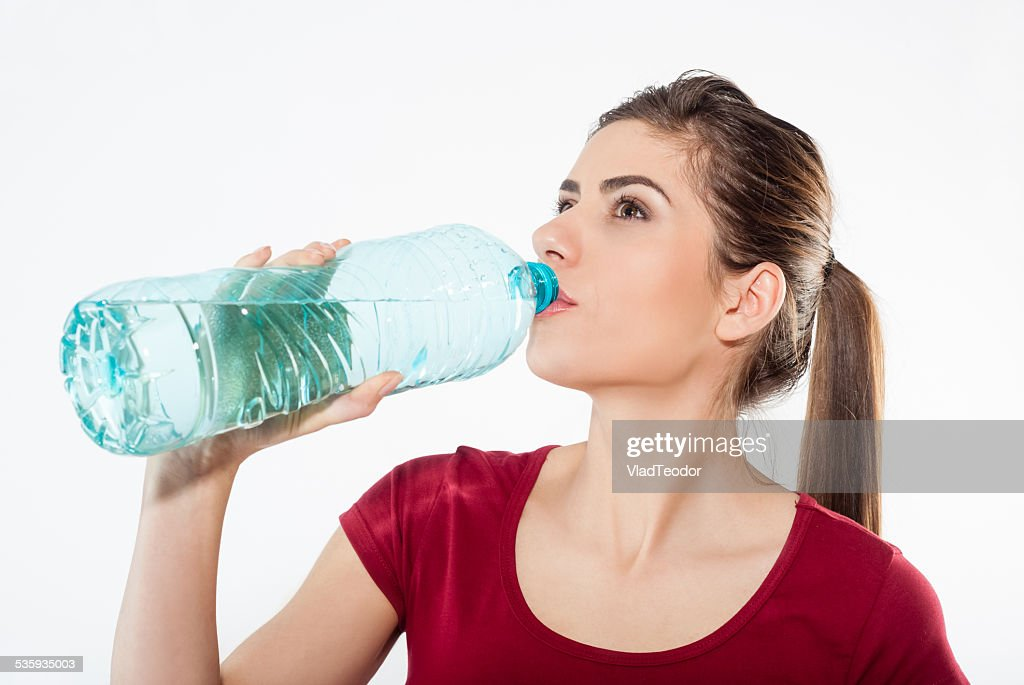 Close-up portrait of young woman drinking water from the bottle. : Stock Photo