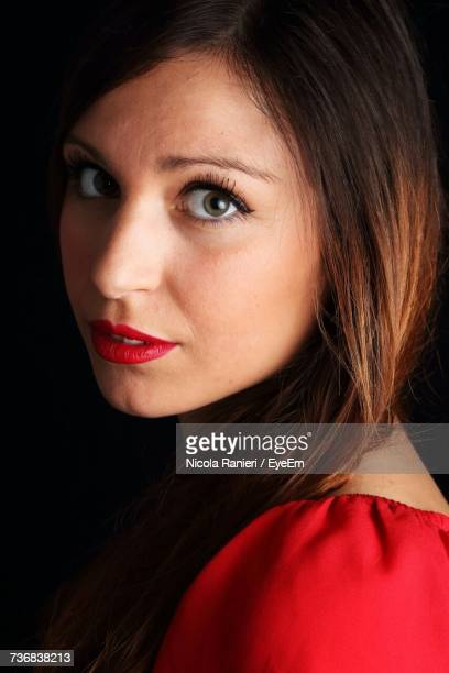 Close-Up Portrait Of Young Woman With Red Lipstick Against Black Background