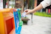 Closeup portrait woman hand throwing crumpled paper in recycling bin.
