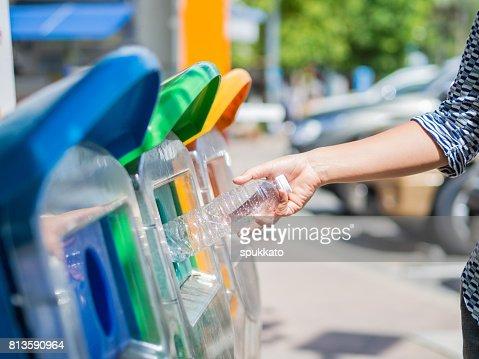 Closeup portrait woman hand throwing empty plastic water bottle in recycling bin. : Stock Photo