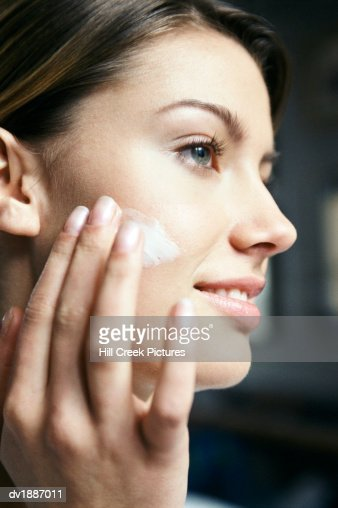 Close-Up Profile of a Young Woman Applying Moisturizer to Her Face : Stock Photo