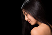 Close-up profile of smiling asian lady with gorgeous black hair in studio. Naked young lady looking down and happy smiling.