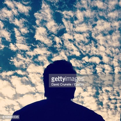 Close-up rear view of a man against blue sky and clouds