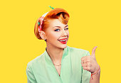 Closeup red head young woman pretty pinup girl green button shirt giving thumbs up sign gesture looking at you camera isolated yellow background retro vintage 50's style. Human emotions body language