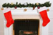 closeup santa stockings on fireplace with garland