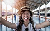 Close-up selfie-portrait of attractive girl with long hair standing at railway station. She is smiling to the camera and shows cool look. Straw hat on head. On holiday and vacation.