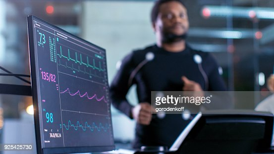 Close-up Shot of a Monitor With EKG Data. Male Athlete Runs on a Treadmill with Electrodes Attached to His Body while Sport Scientist Holds Tablet and Supervises EKG Status in the Background. : Foto de stock