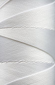 A close-up shot of a white spool of thread