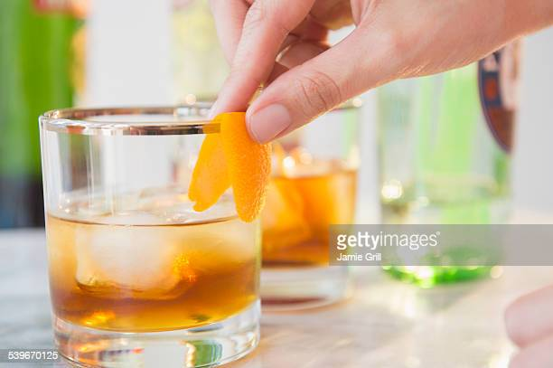 Close-up shot of bartenders hand decorating cocktail glass with orange peel