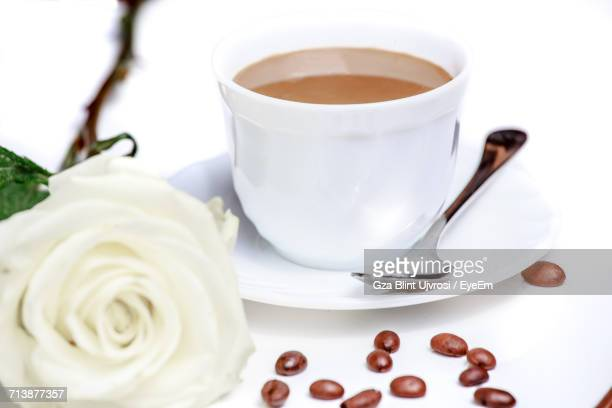 Close-Up Shot Of Coffee In Cup By Rose Flower On White Background