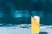 close-up shot of glass of tasty orange cocktail on poolside