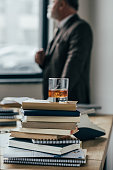 close-up shot of glass of whiskey on stack of books with senior man standing blurred on background