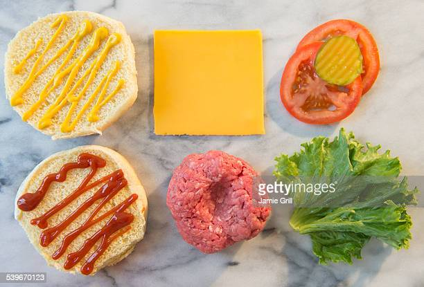 Close-up shot of hamburger ingredients in rows on table