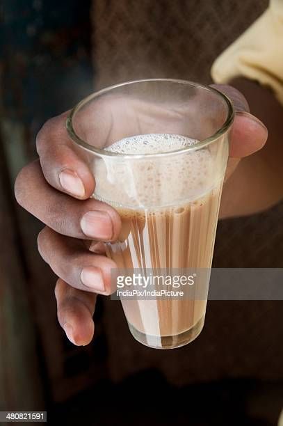 Close-up shot of male's hand holding glass of Indian milk tea