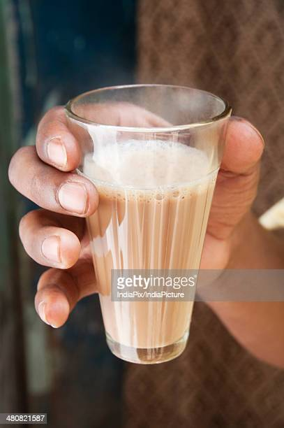 Close-up shot of man's hand holding glass of chai