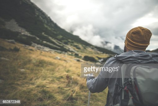 Close-up shot of traveler walks alone in mountains : Stock Photo
