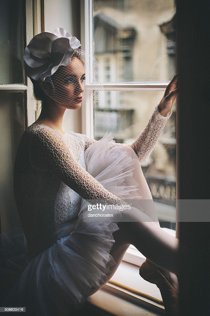 Closeup shot of young balerina looking trough the window : Stock Photo
