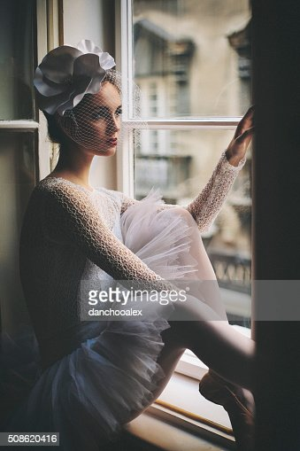 Closeup shot of young balerina looking trough the window : Stock Photo