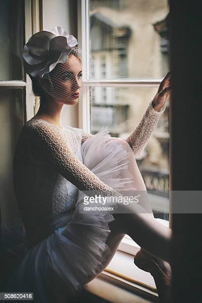 Closeup shot of young balerina looking trough the window