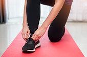 closeup sport woman doing tie shoes