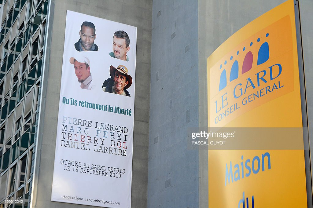 A close-up taken on January 17, 2013 in Nimes, southern France, shows the poster hung during a ceremony, on the facade of the General Council building in support to the four French hostages (LtoR, top to bottom: Thierry Dol, Marc Feret, Pierre Legrand and Daniel Larribe) captured in Niger and detained since 28 months in Mali by AQIM. The hostages were in a group of seven captured in Niger's uranium-mining town of Arlit. The 'Serval' French military operation backing Mali's army in battling Islamist insurgents currently has some 1,400 soldiers deployed, some of whom are engaged in ground operations. AFP PHOTO / PASCAL GUYOT