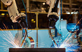 Close-up team robots are welding assembly metal part in factory