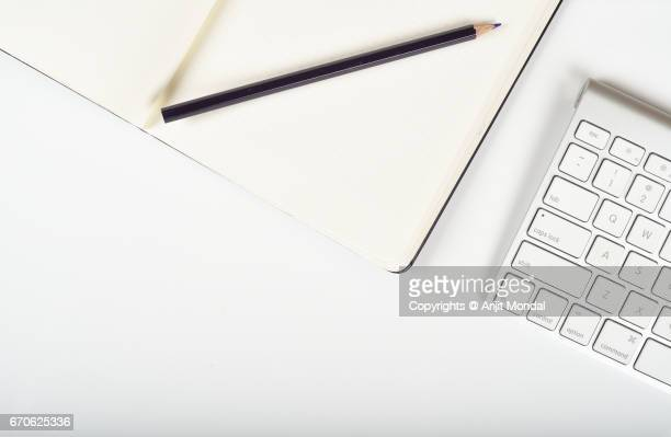 Close-up Top View of Bluetooth Keyboard with Copy, Pencil White Background