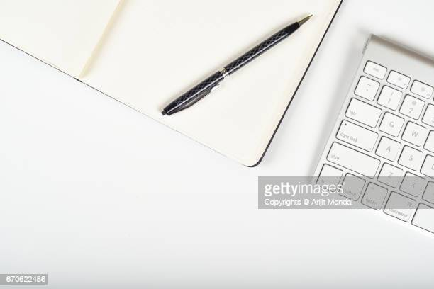Close-up Top View of Cropped Bluetooth Keyboard on White Office Table with Notepad and Pen